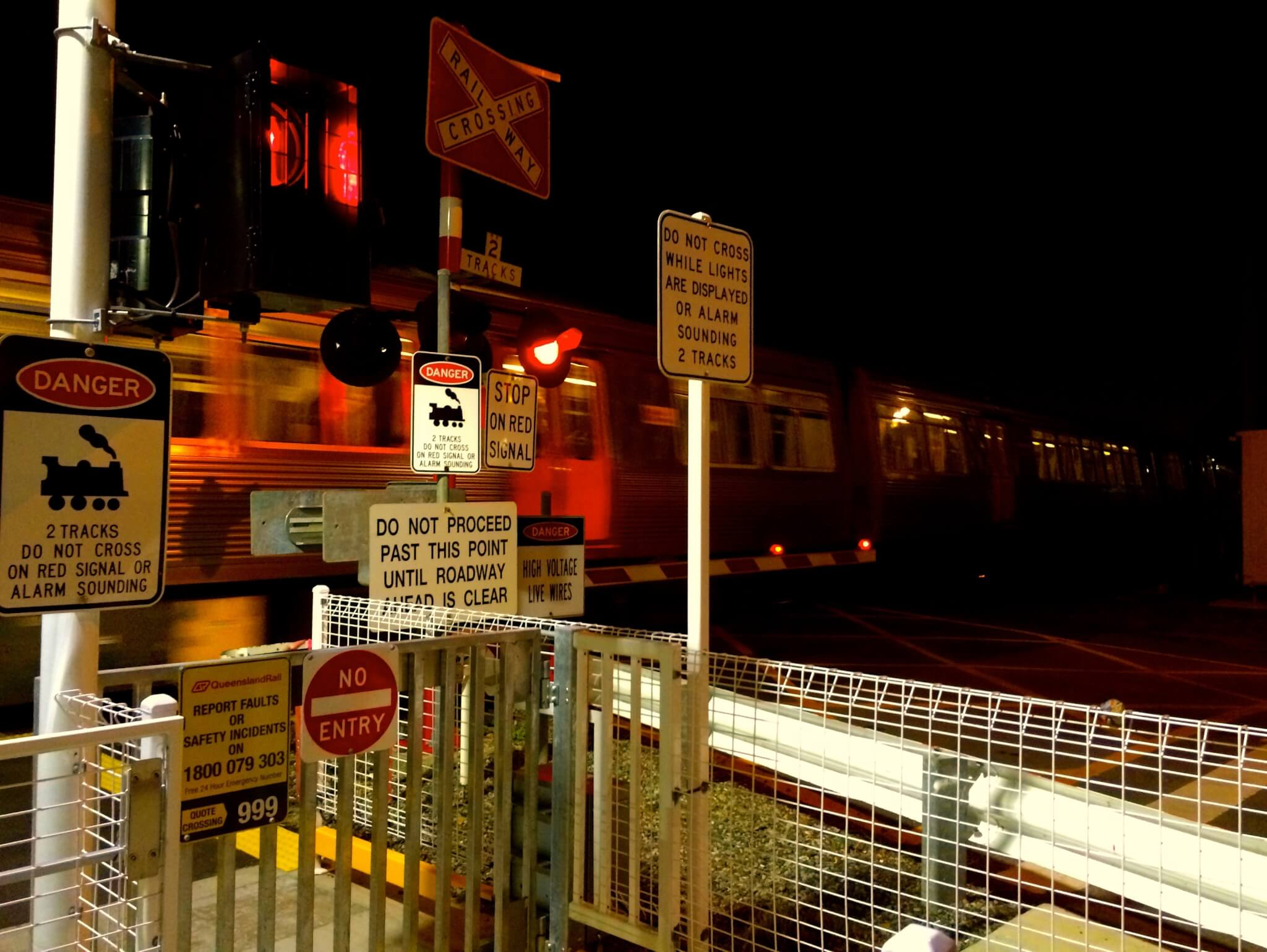 A level crossing in Queensland with many signs.