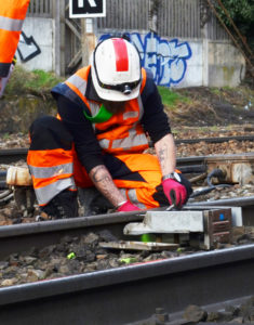 Zöllner automatic track warning system: Operator mounting a train detector on the track