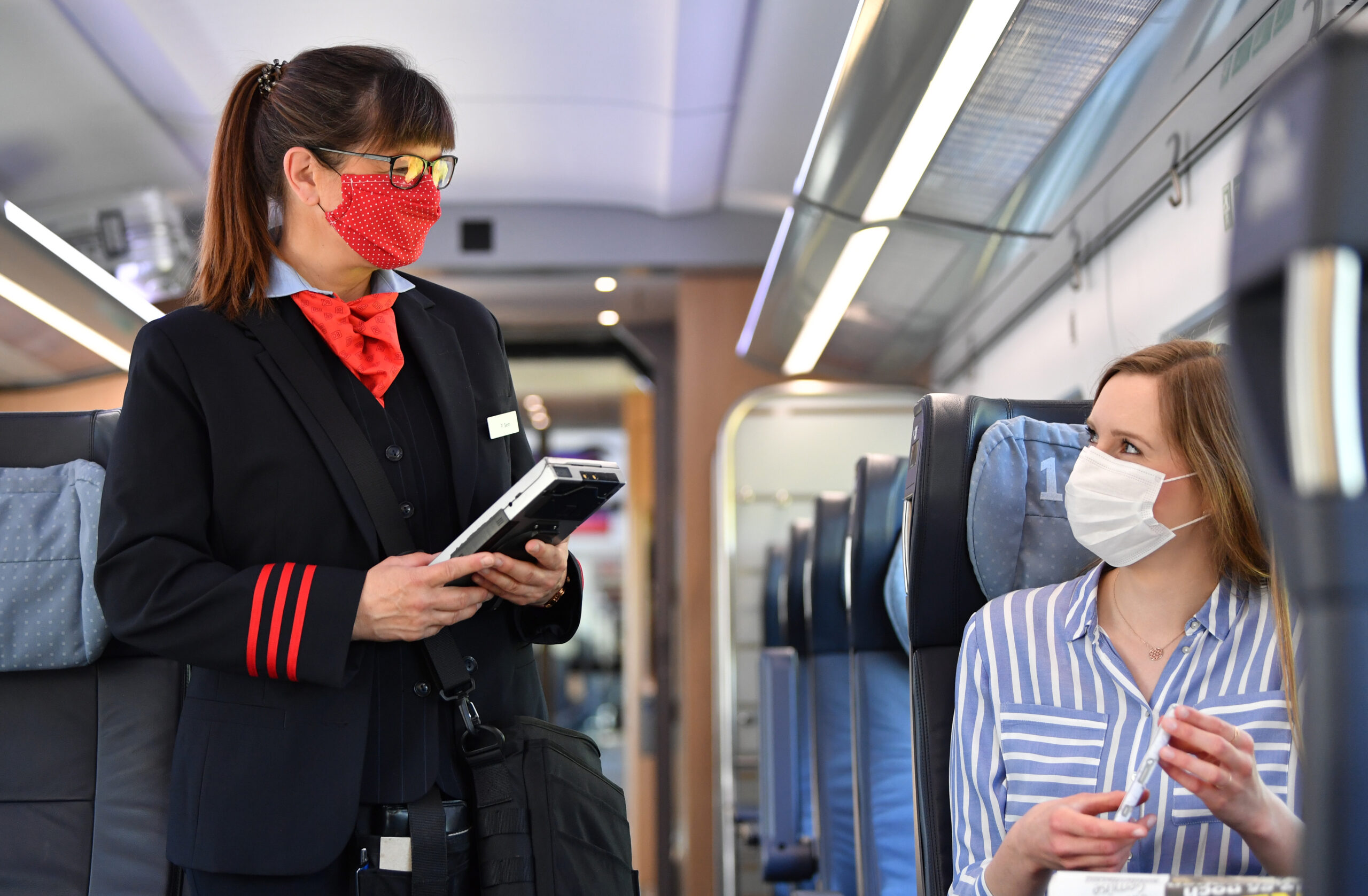 Contactless ticket check: staff and passengers wear masks during the coronavirus pandemic