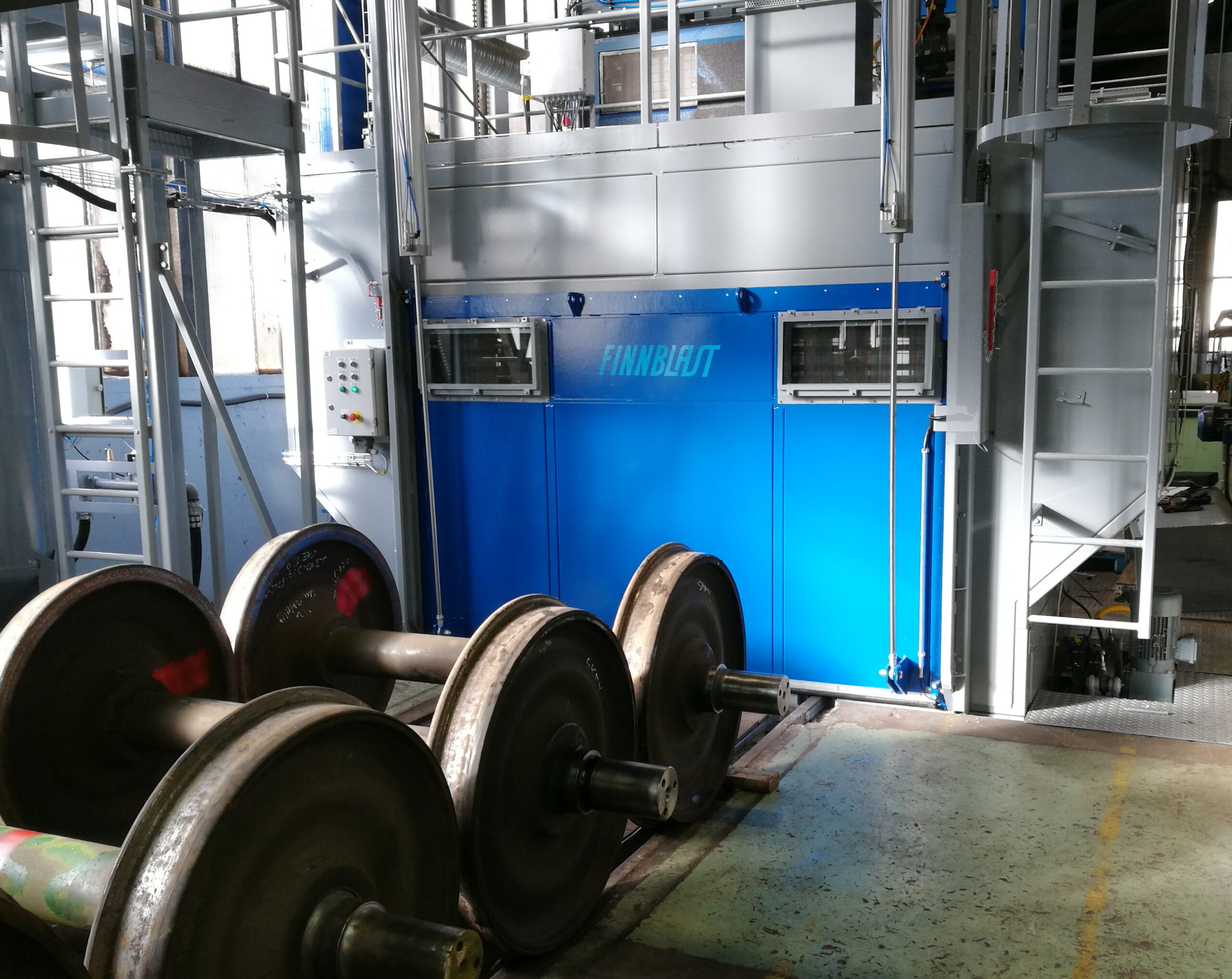 A drive-through machine for blast cleaning of wheelsets