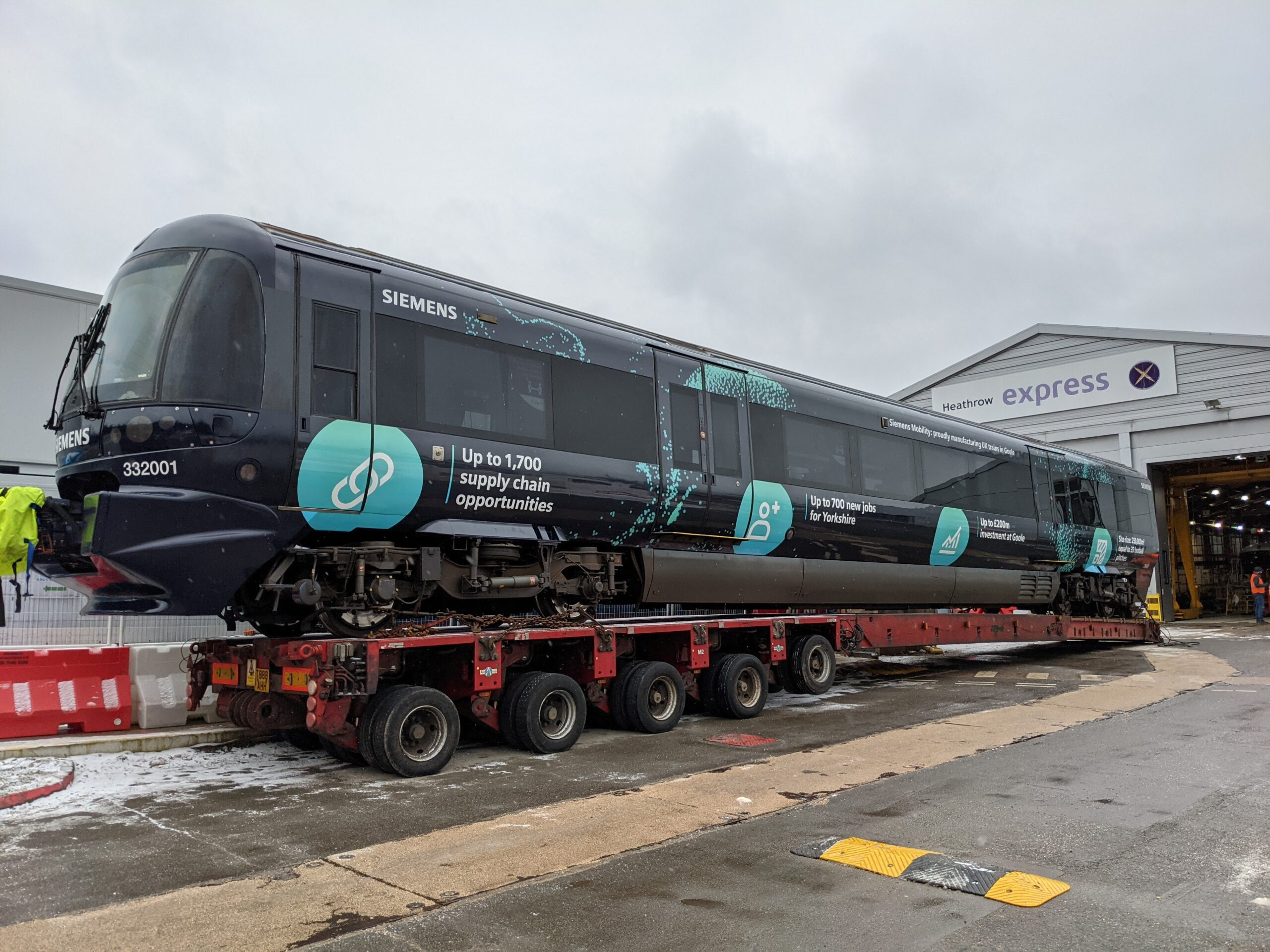 Heathrow Express train leaves its depot on a low loader