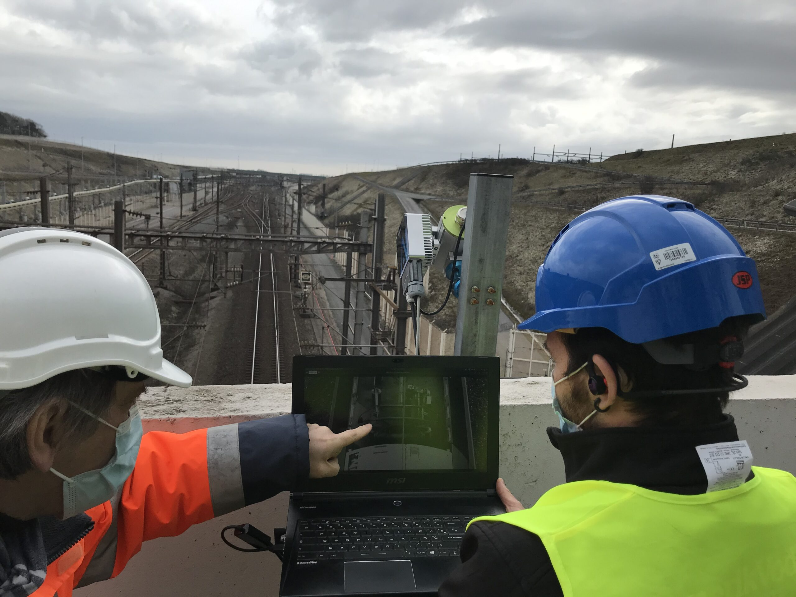 The client is showing with its finger the output of the real-time pantograph analysis performed at Eurotunnel.