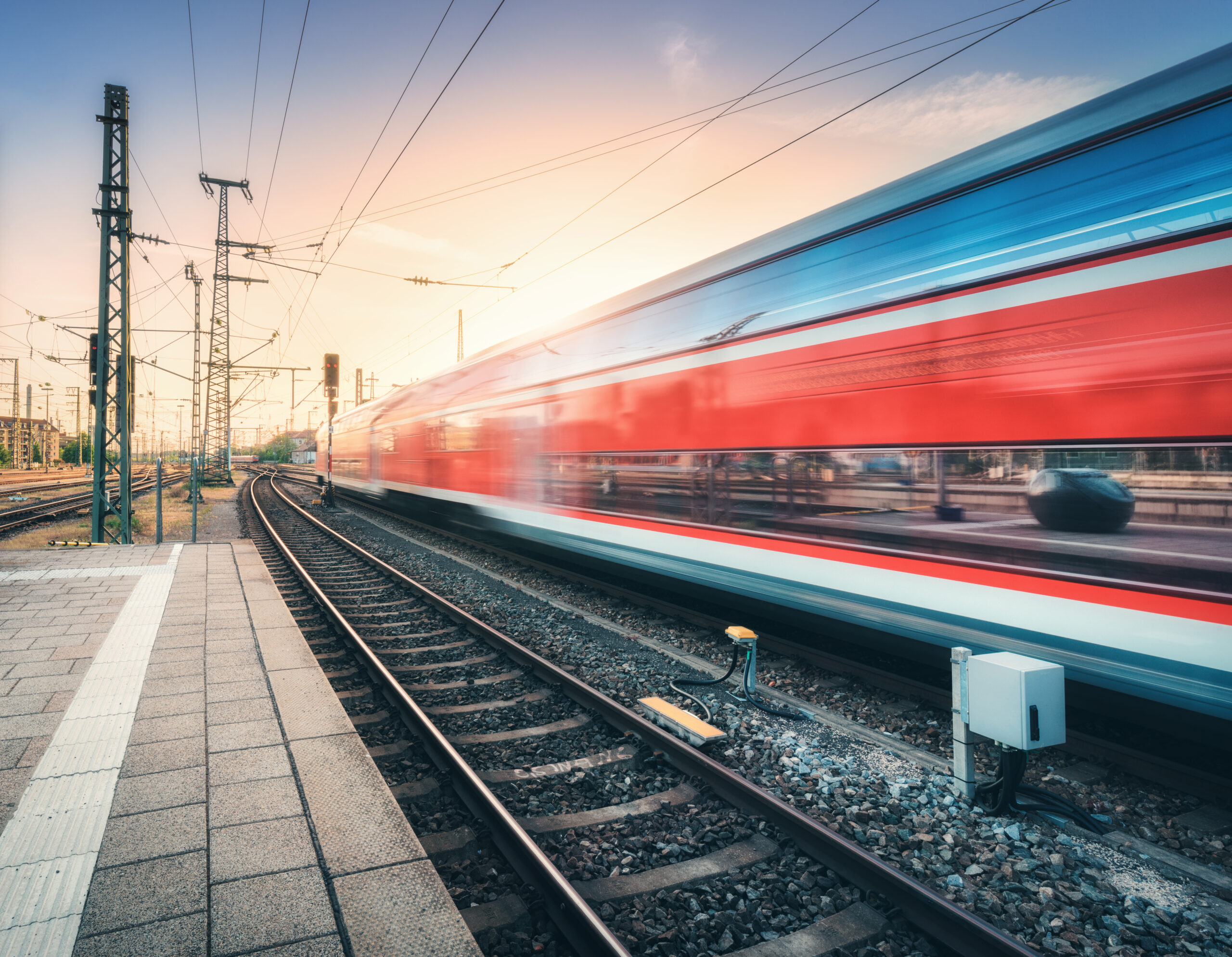 Red high speed train in motion on the railway station at colorful sunset. Blurred modern intercity train with sky reflection in windows on the railway platform. Passenger transportation. Railroad