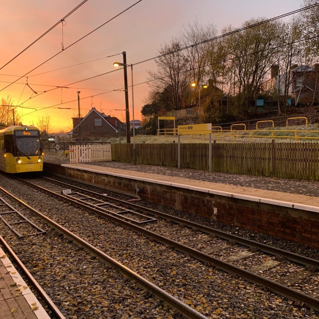 Bury tram pulling into Whitefield Metrolink stop at sunrise