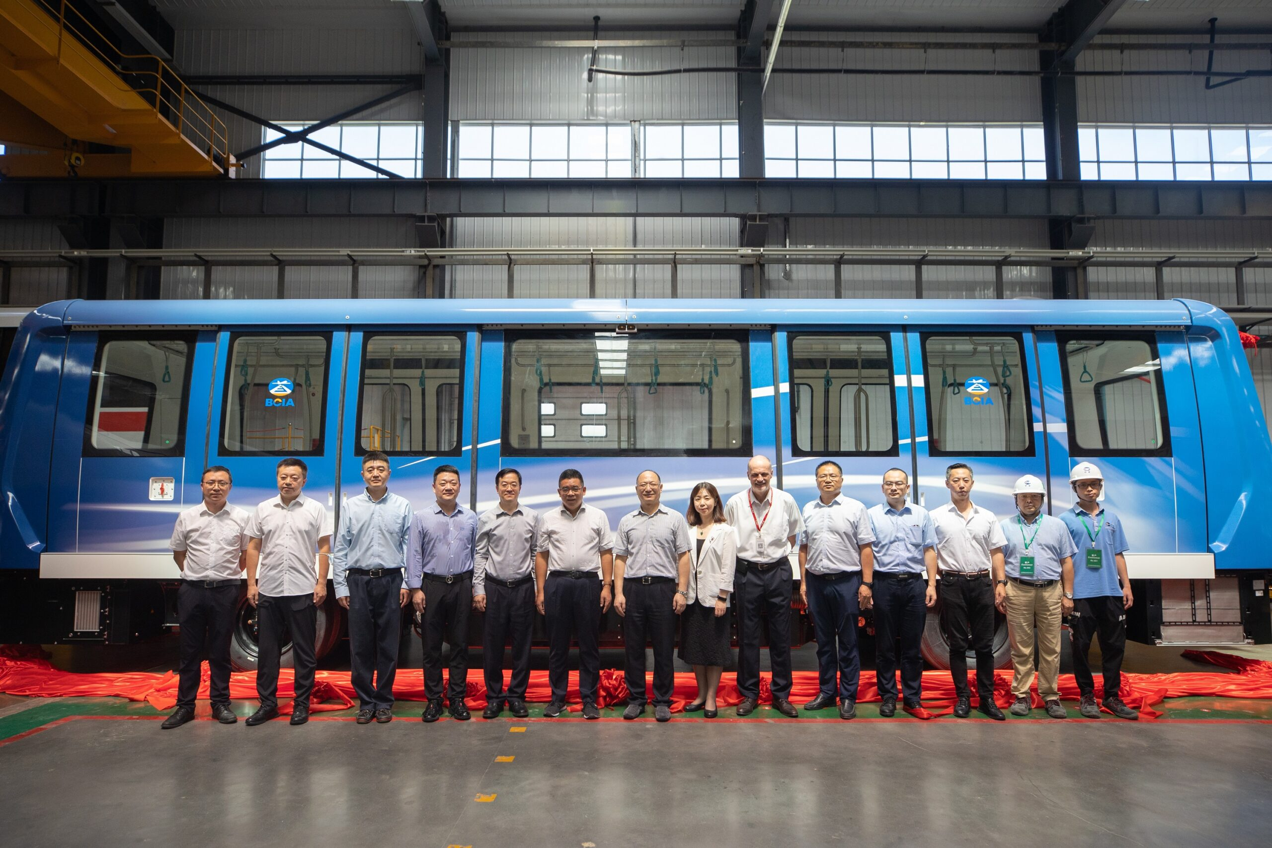 Group photo in front of the new automated people mover for Beijing Capital International Airport